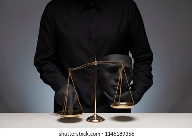 Man holding black evil mask in one hand pressing the scale on the gray background with invisible face, scale on the wooden desk, law and justice.