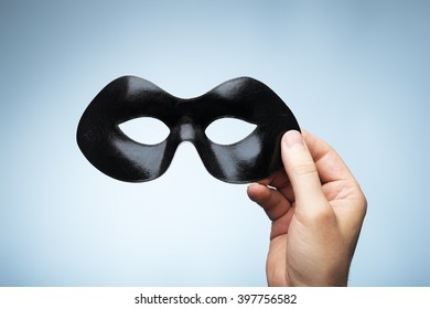 Man holding a black eyemask in his hand.