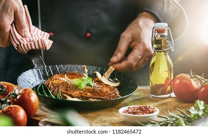 Man holding black frying pan containing cooked meat and vegetables with napkin while it sits on cutting board