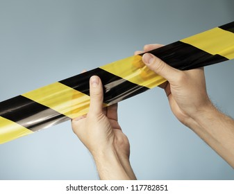 Man holding black and yellow striped barrier tape in his hands.