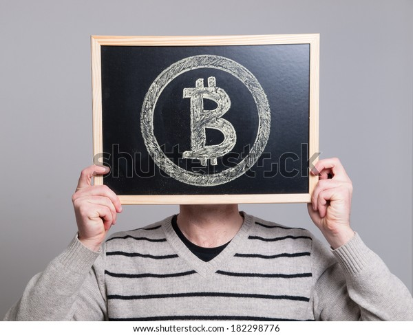 man holding a blackboard with bitcoin symbol isolated on grey background.