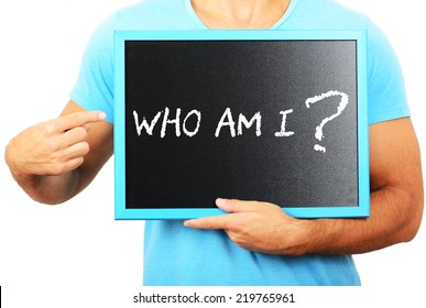 Man holding blackboard in hands and pointing the word WHO AM I