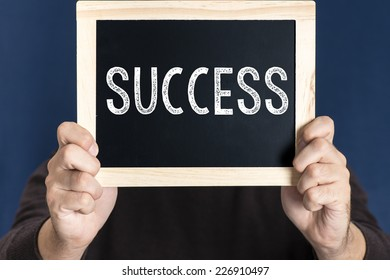 Man holding blackboard with word success