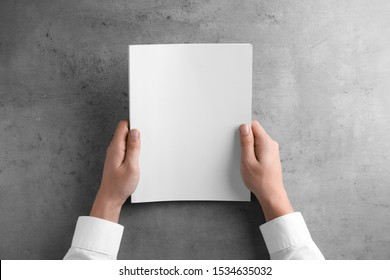 Man holding blank booklet at grey table, top view. Mock up for design