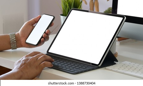 Man holding blank screen mobile phone while working with Smart Keyboard of tablet