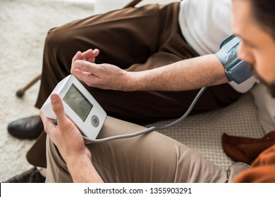 man holding blood pressure meter while measuring blood pressure of senior father