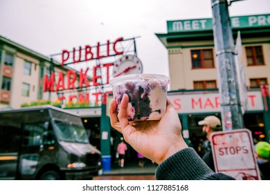 Man holding a bluberry ​yogurt cub at Pike Public Market, Seattle, Washington, USA (April 5, 2018)
