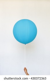 Man holding blue balloon on a white background.
