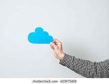 Man holding blue cardboard model of cloud. Idea for high technology, cloud technology