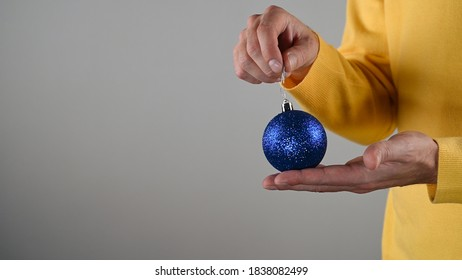 A man holding a blue christmas ball in his hand