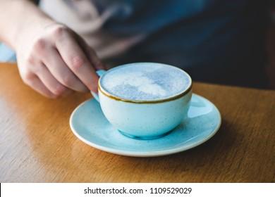 Man holding blue matcha tea latte in cafe.