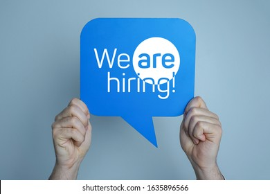 Man holding blue speech bubble says we are hiring.