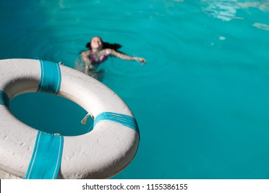 Man holding a blue and white life saver out to help save a drowning woman in a swimming pool. Lifeguard holding life preserver out to a person in distress in an outdoor swimming pool.