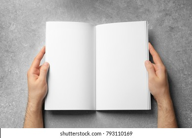 Man holding book with blank pages on grey background. Mock up for design