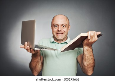 man holding a book in one hand and a laptop in the other. He does not know what to prefer. on a gray background