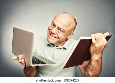 man holding a book in one hand and a laptop in the other, on a gray background
