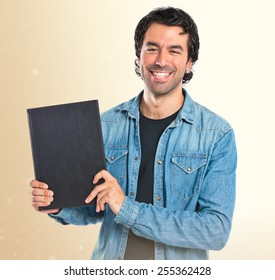 Man holding a book over ocher background