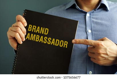 Man is holding book with title Brand Ambassador.
