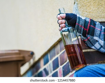 a man is holding a bottle of alcohol outside in his hand