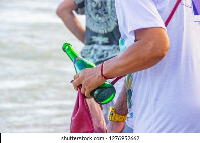 man holding bottle of champagne, during the iemanja party in copacabana in Rio de Janeiro Brazil.