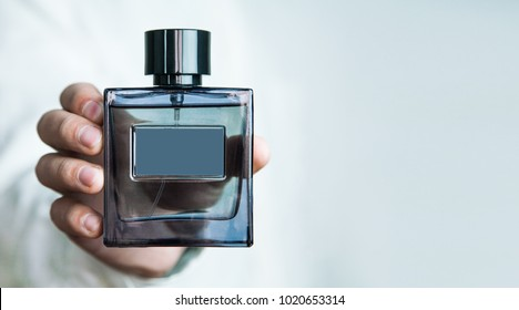 Man holding a bottle of perfume.