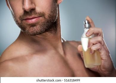 Man holding up bottle of perfume