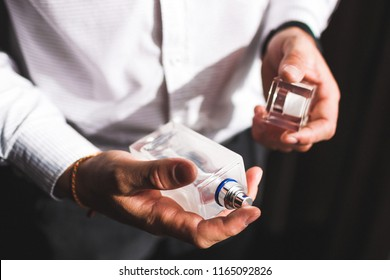 Man holding bottle of perfume and smells fragrance