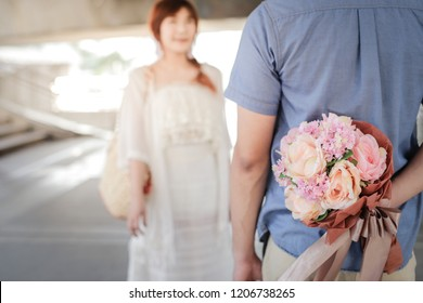 A man holding bouquet of flowers for surprising his girlfriend for valentine's day