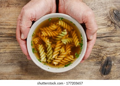 Man holding a bowl of soup.