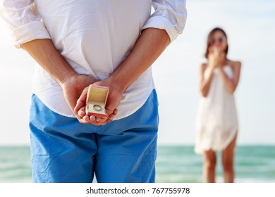 Man holding box with marriage ring making propose to his girlfriend at the beach, Love and marriage concept, Selective focus