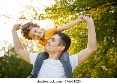 Man holding boy on shoulders and having fun in park.