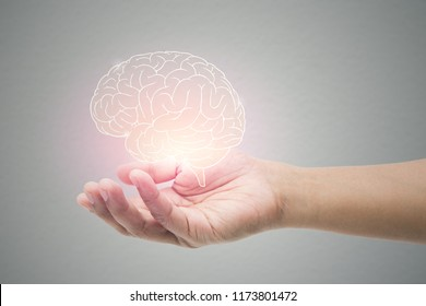Man holding brain illustration against gray wall background. Concept with mental health protection and care. - Shutterstock ID 1173801472