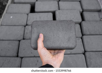 Man holding a brick. Stack of paving stone on construction site. Bricks for paving stones stacked in stacks, background texture structure. Gray pavement bricks for pavement road.