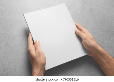Man holding brochure with blank cover on grey background. Mock up for design