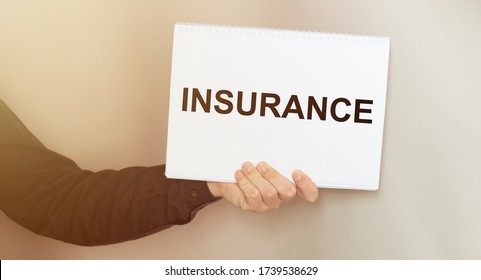 Man holding brochure with INSURANCE text on grey background. Mock up for design