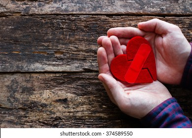 man holding a broken heart glued on a wooden background