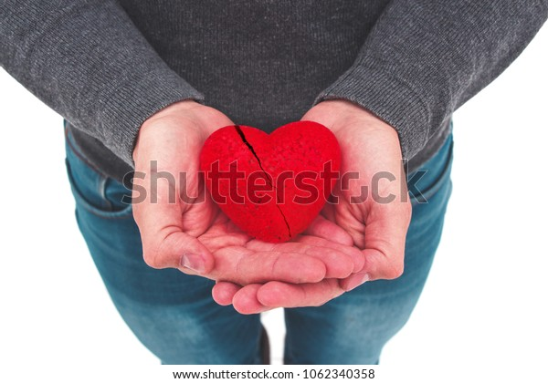 Man is holding a broken heart in his hands. Cardiovascular disease. Unrequited love. Helping hand.