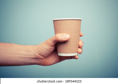 A man is holding a brown paper cup