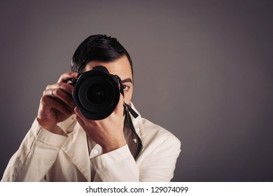 Man holding camera over dark background.