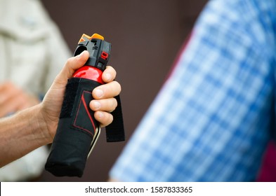 Man holding a can of pepper bear spray up close blurred background room for text