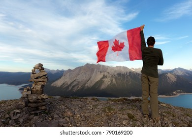 Man holding Canada flag on mountain. There is an inukshuk beside the man. Canadian flag blowing in the wind with views of mountains in the background.