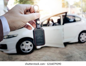 Man holding car key with blur image of white car on background.