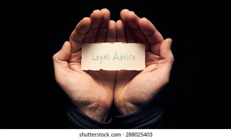 A man holding a card in cupped hands with a hand written message on it, Legal Advice.