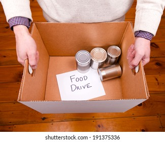 A man holding a cardboard box containing a few tin cans for a food drive.