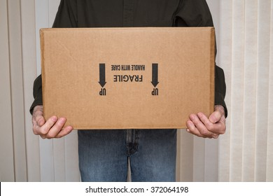 "Man holding cardboard box marked ""fragile, handle with care"" upside down."