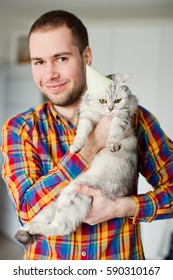 Man holding cat with party hat