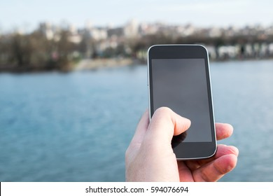 man holding a cell phone with the river in the background