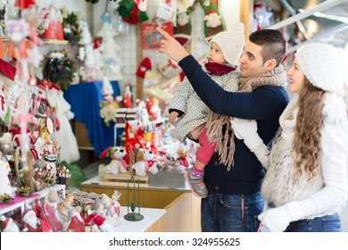 A man holding a child with his wife are standing at a counter at a christmas fair and pointing at christmas decorations.