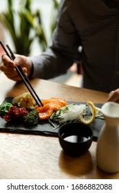 Man holding a chopstick with salmon sashimi on restaurant table. Asian man eating sashimi set in Asian restaurant.