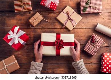 Man holding Christmas presents laid on a wooden table background